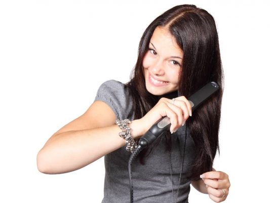 Lady using a titanium flat iron on her straight hair